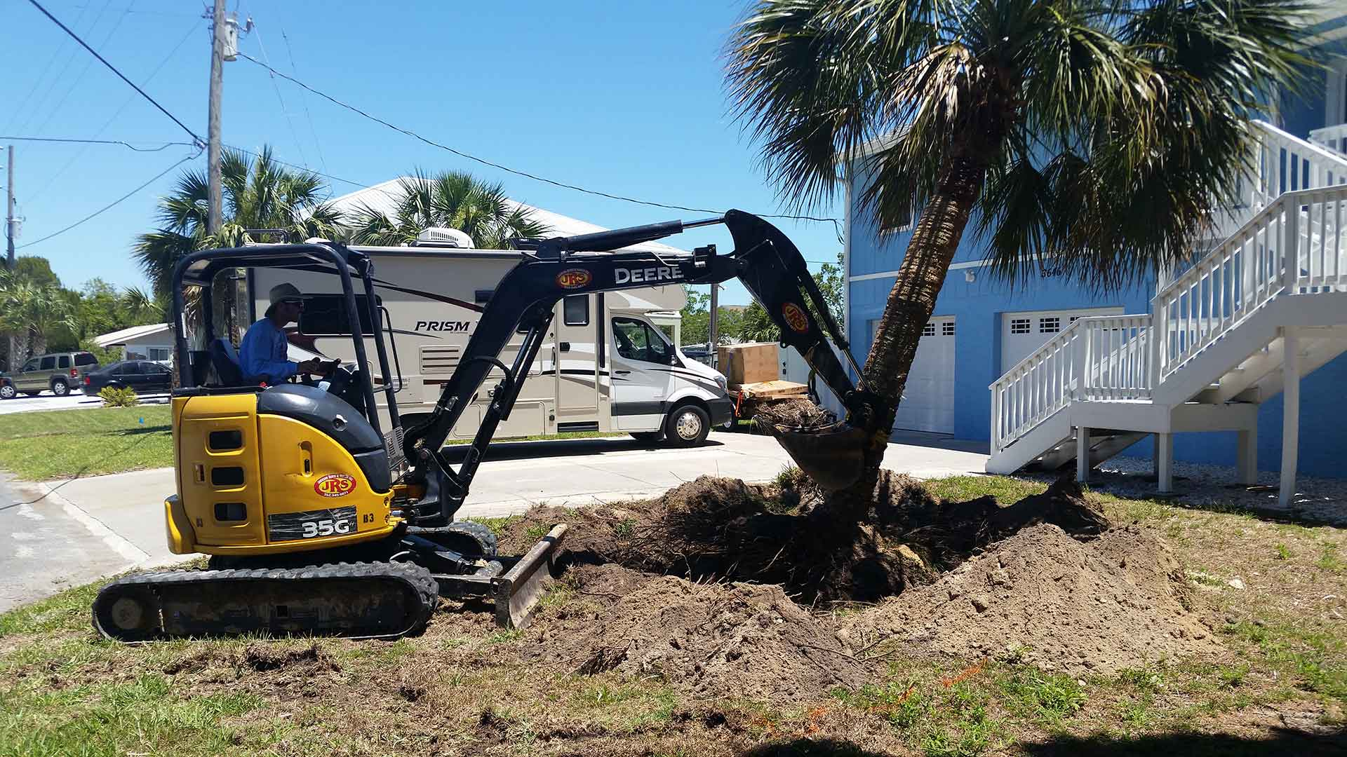 Team member using heavy machinery to knock over a small tree that will be replaced.