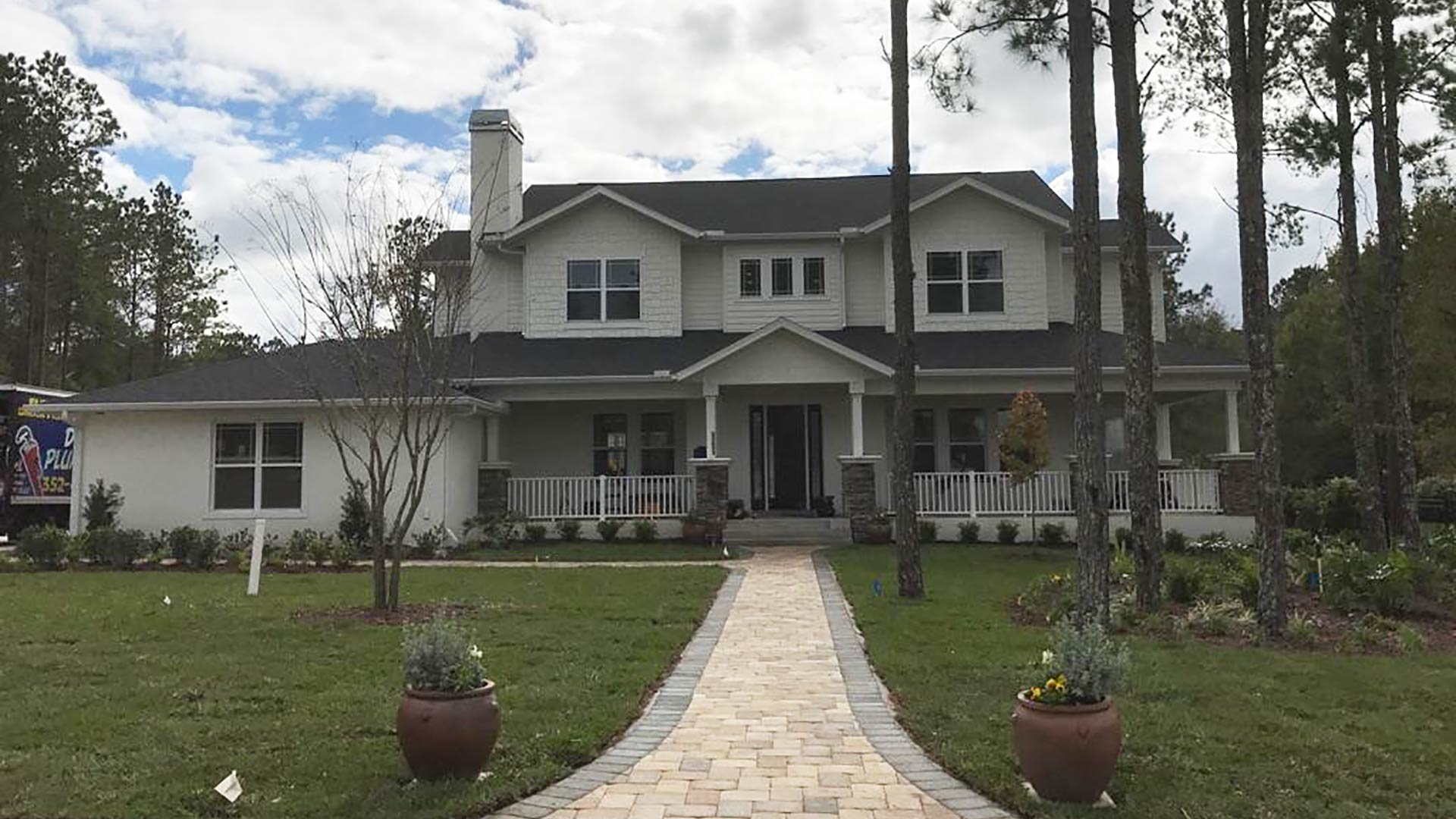 This residential property has a well manicured lawn and landscaping, and a paver walkway.